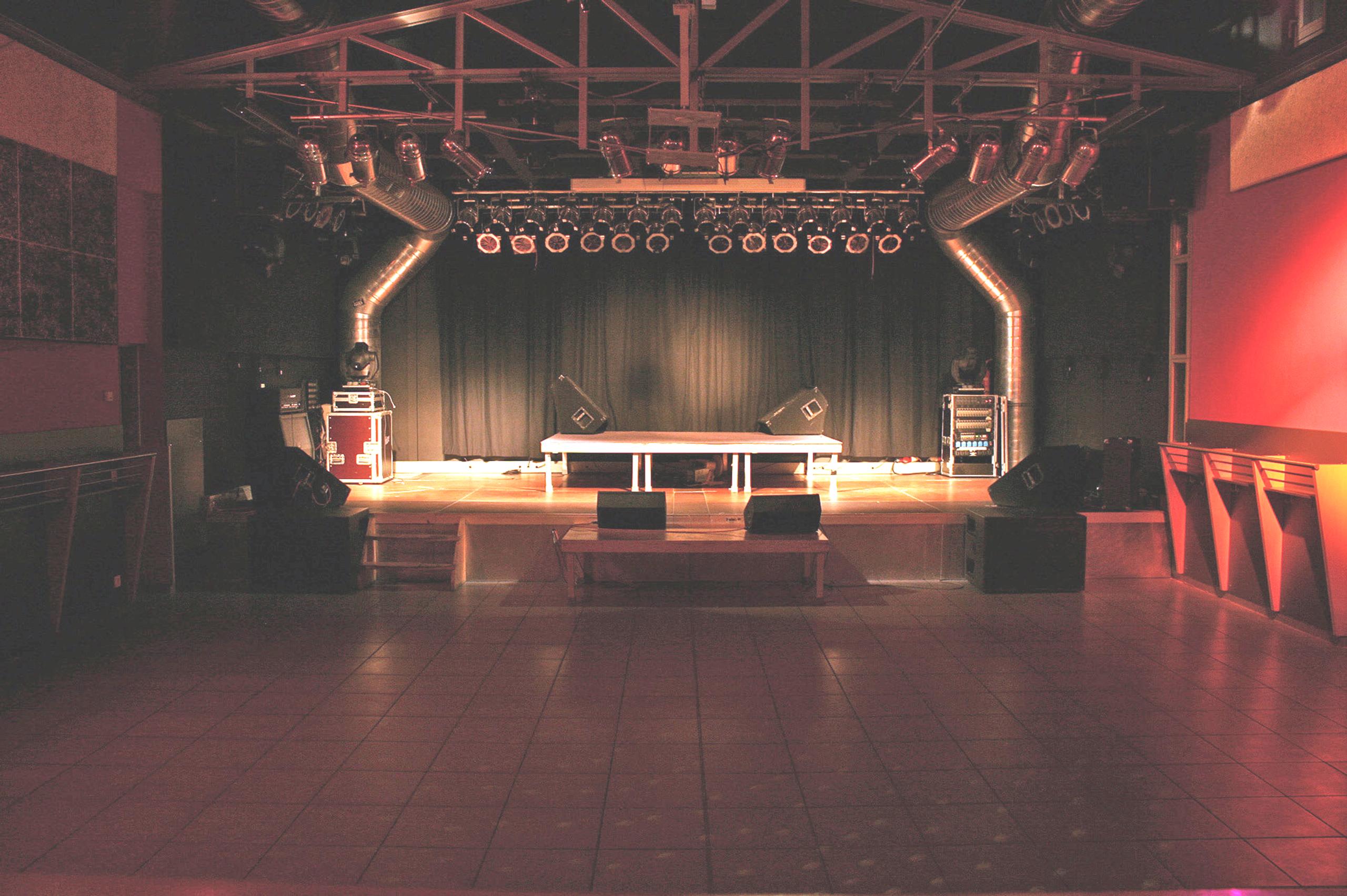 Foto von einem leeren Konzertsaal der LUISE mit einer beleuchteten Bühne. Über der Bühne hängen viele Scheinwerfer.