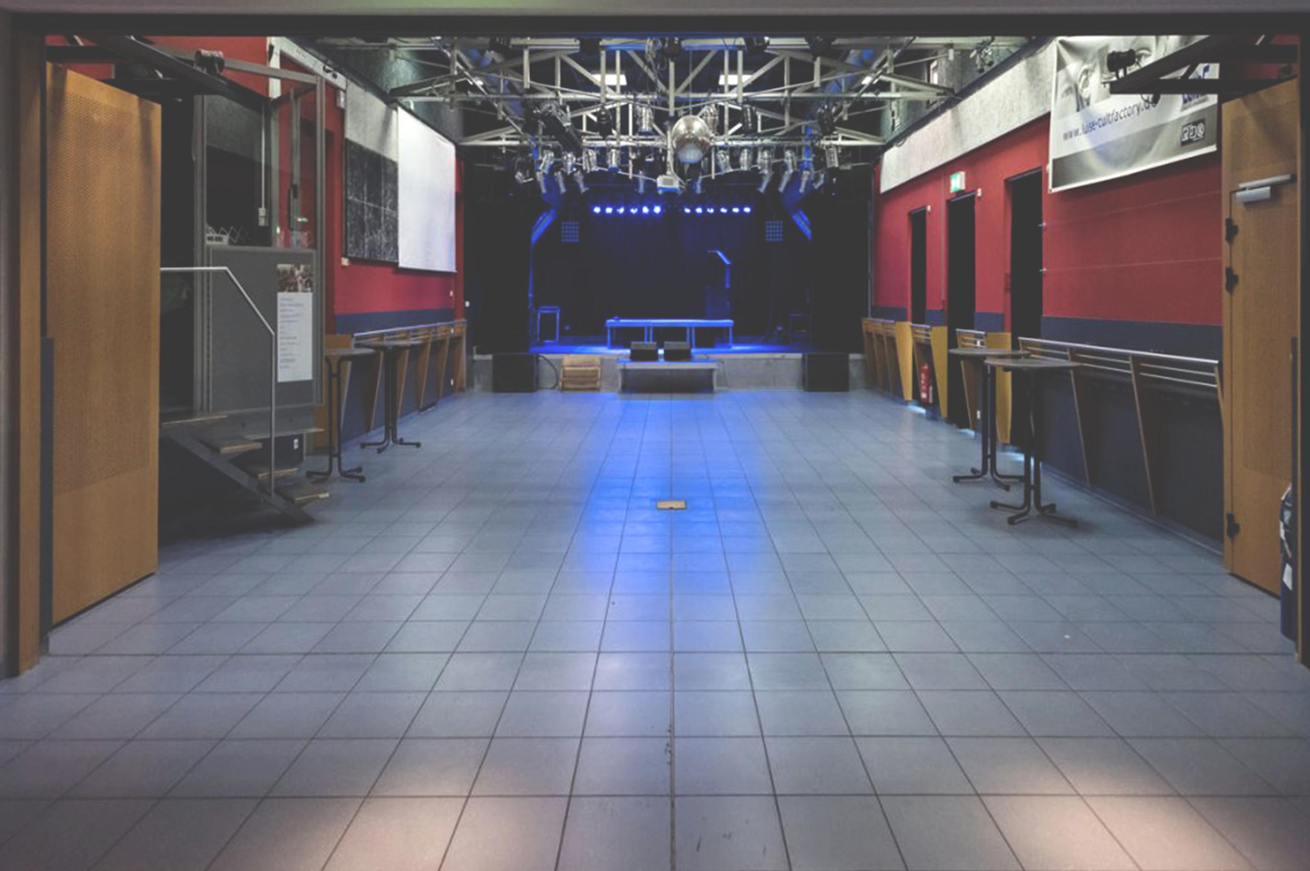 Foto von dem leeren Konzertsaal der LUISE mit einer beleuchteten Bühne bei geöffneter Trennwand. Über der Bühne hängen viele Scheinwerfer. Links eine Lichtkanzel.