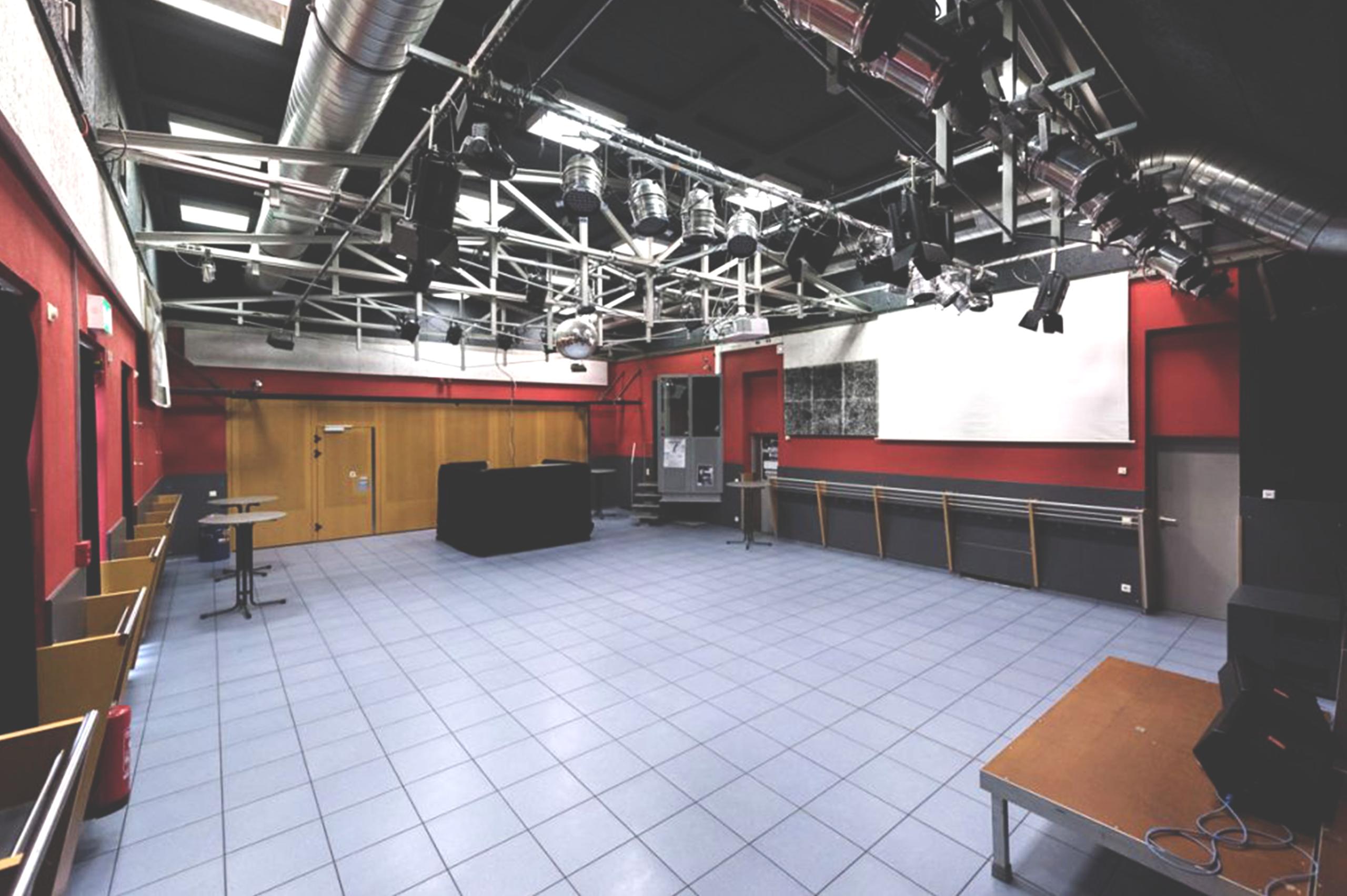 Foto von dem leeren Konzertsaal der LUISE. Eine Lichtkanzel an der rechten Wand. Am anderen Ende des Saals steht der FoH (Front of House: erhöhter Platz, von dem aus Tontechniker bei einer Veranstaltung arbeiten)