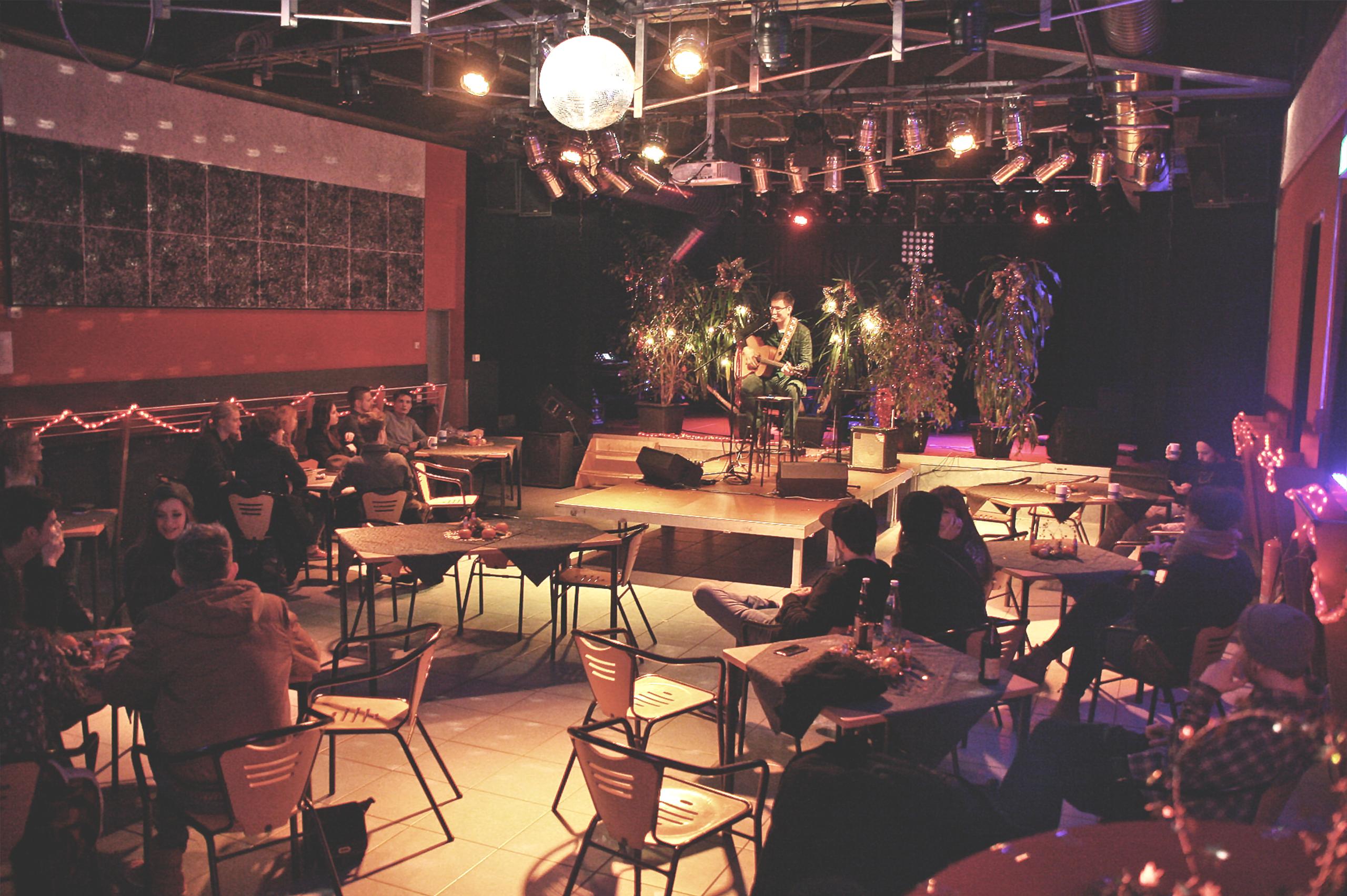 Foto von einer Veranstaltung im LUISEN Saal. Auf einer Bühne sitzt ein junger Musiker mit Gitarre. Im Zuschauerraum um ihn herum stehen Tische mit Stühlen, auf denen viele Personen sitzen.