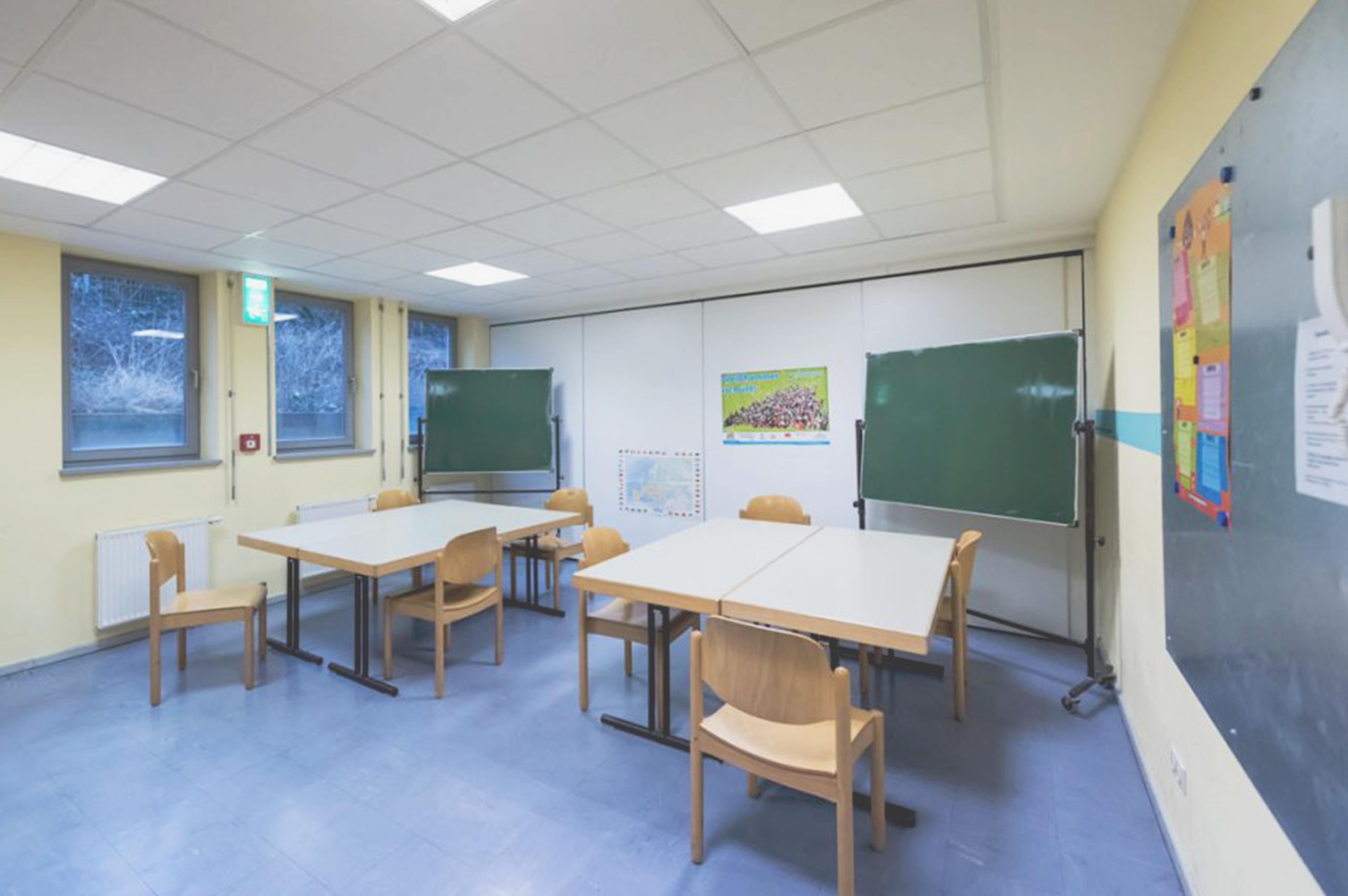 Foto vom Mehrzweckraum. Zwei große Tische mit Stühlen stehen im Raum. An der hinteren Wand stehen zwei Tafeln.