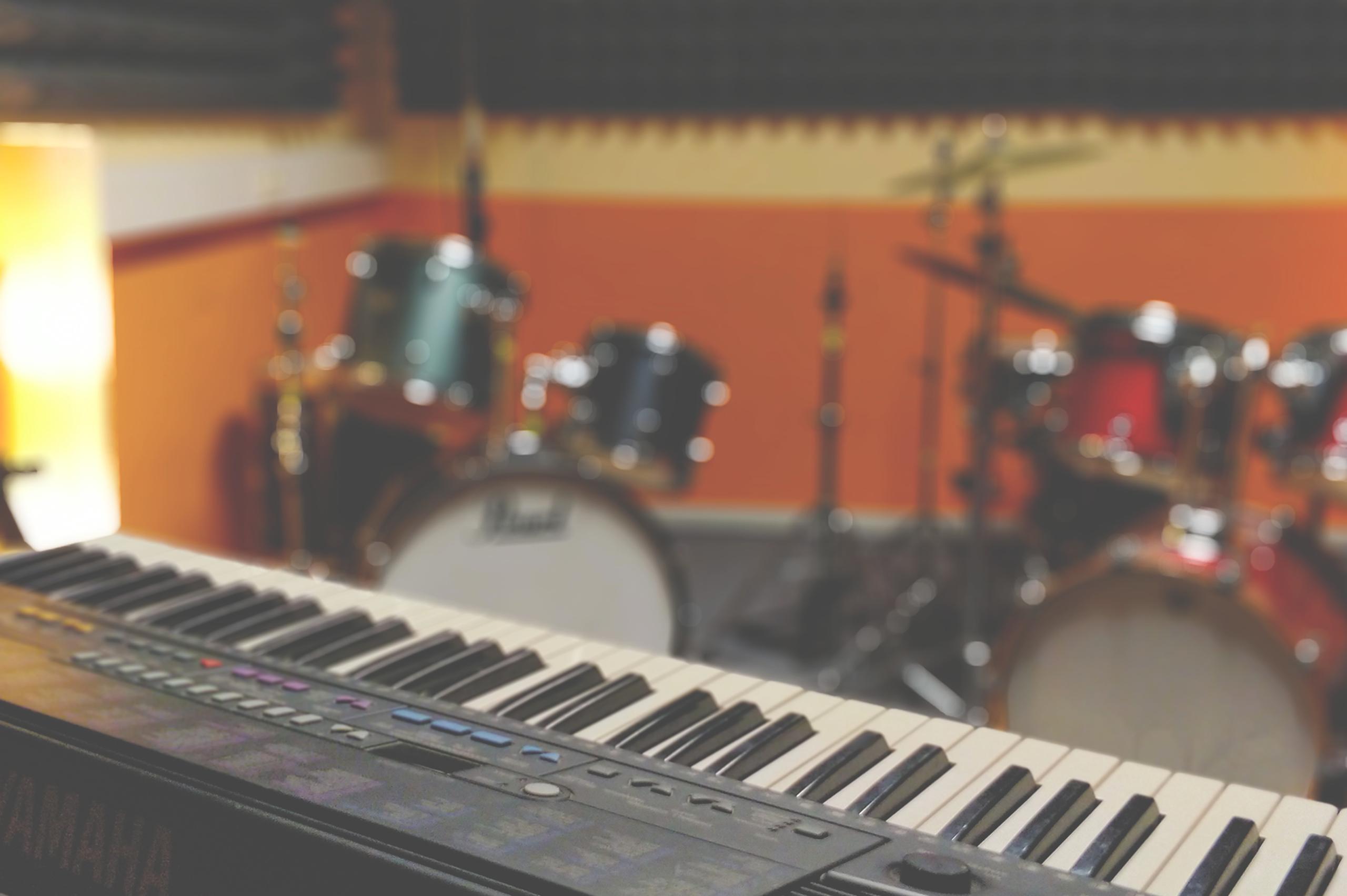 Foto eines Proberaumes mit einem keyboard im Vordergrund und zwei Schlagzeugen im Hintergrund.