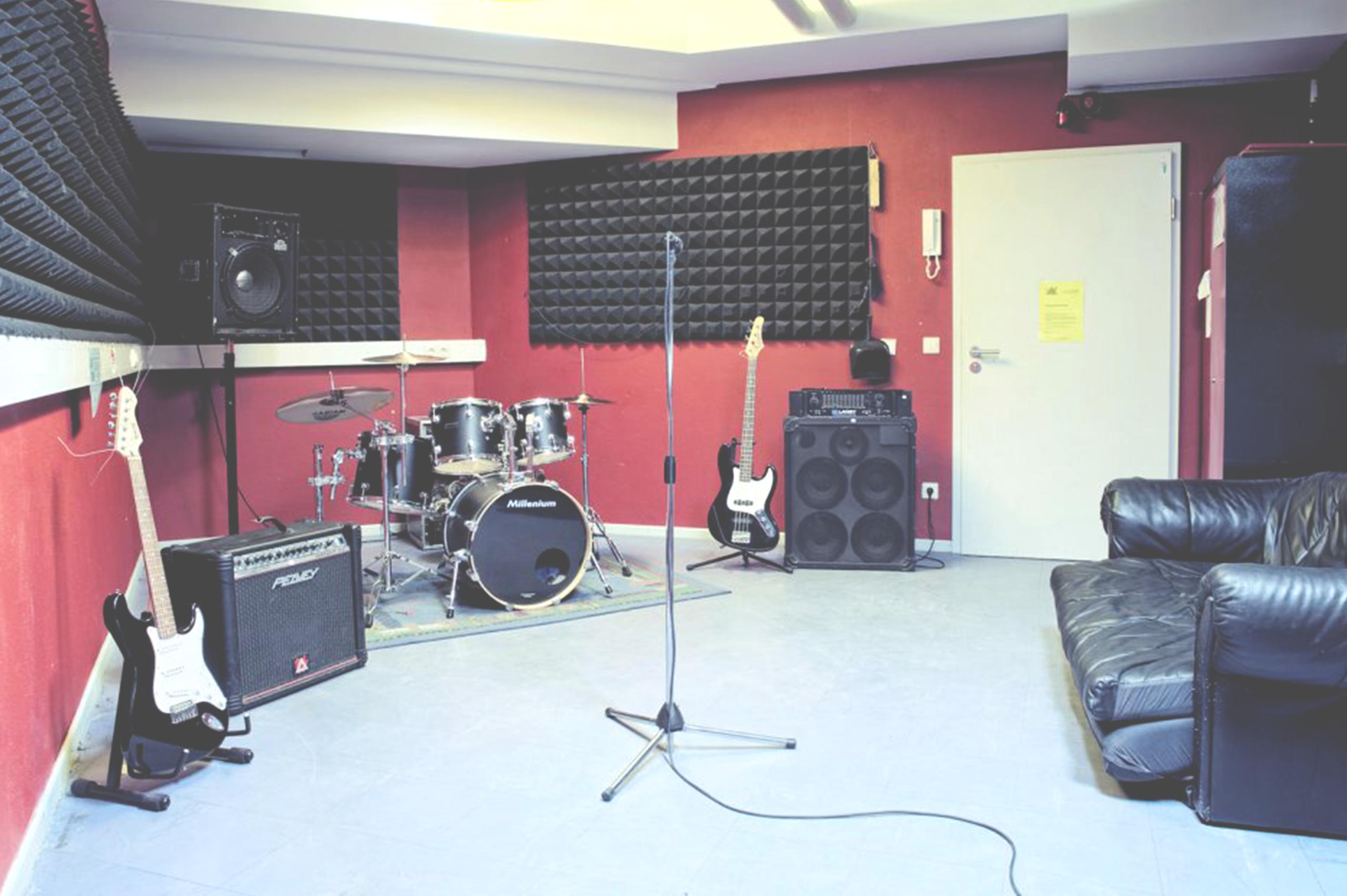 Foto eines Proberaumes mit zwei E-Gitarren, einem Schlagzeug, Verstärkern udn einer Ledercouch.