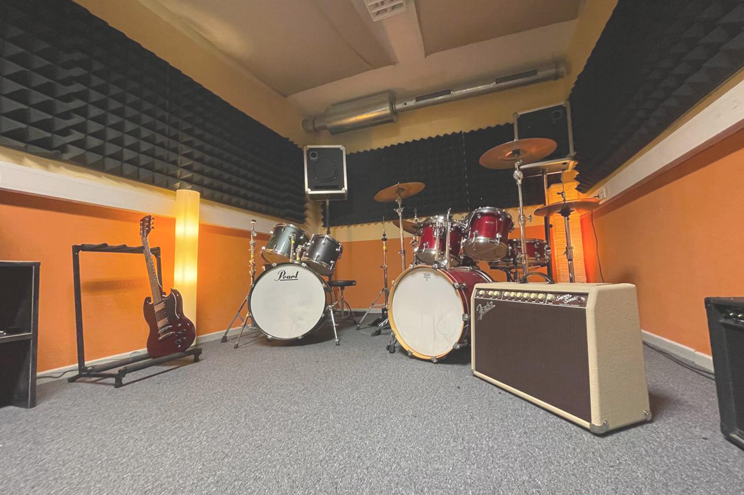 Foto eines Proberaumes mit zwei Schlagzeugen, einem Verstärker im Vordergrund und einer E-Gitarre im Hintergrund.