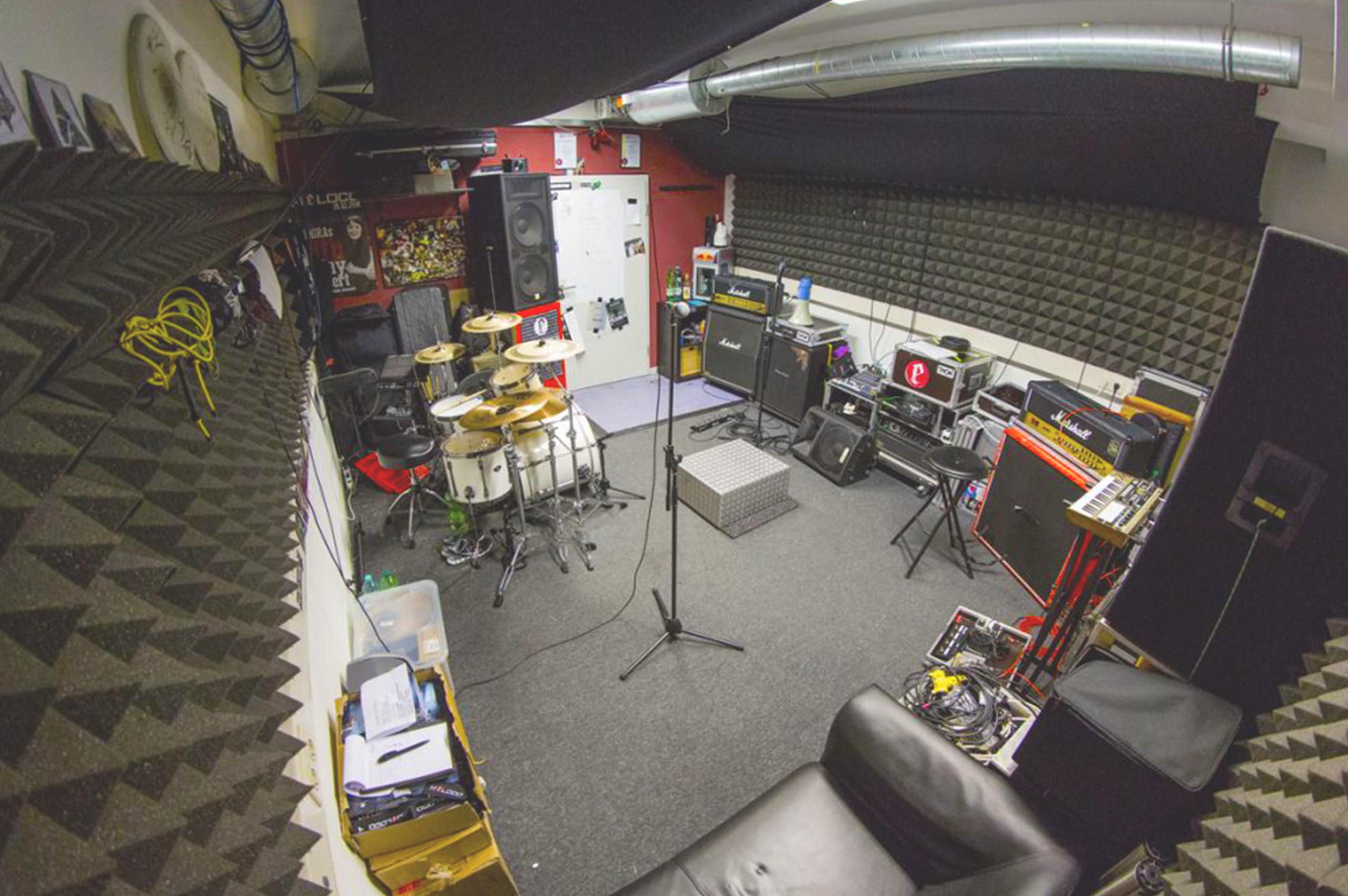 Foto eines Proberaumes mit vielen Instrumenten und unterschiedlicher Tontechnik.