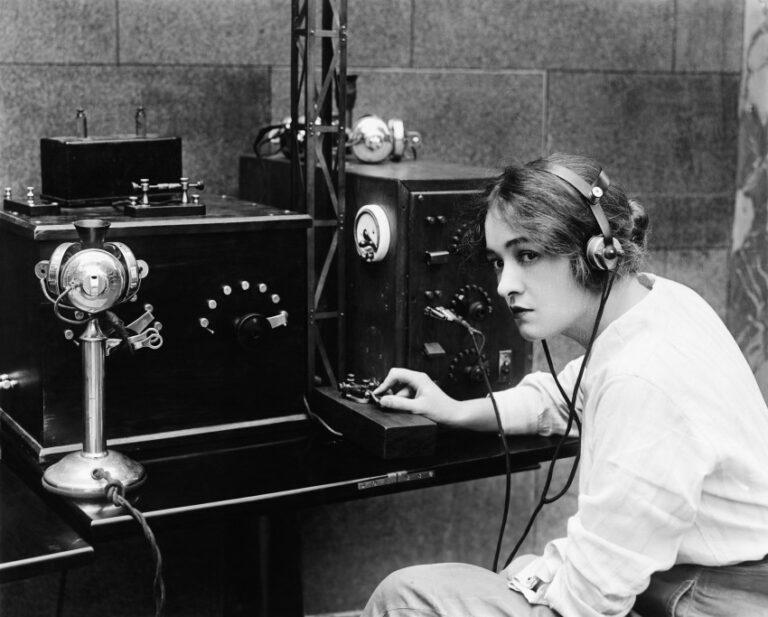 EIn altes Foto von einer Frau vor einem Telegraphen
