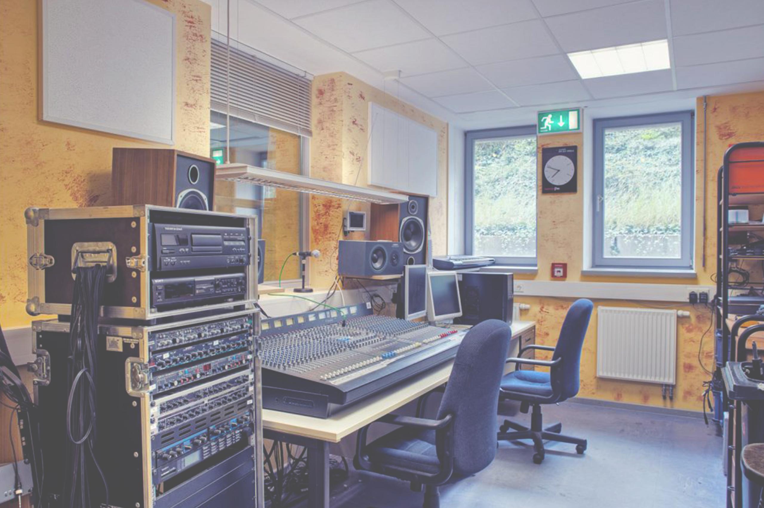 Foto des Tonstudios. Zwei Bürostühle und ein großes Mischpult.