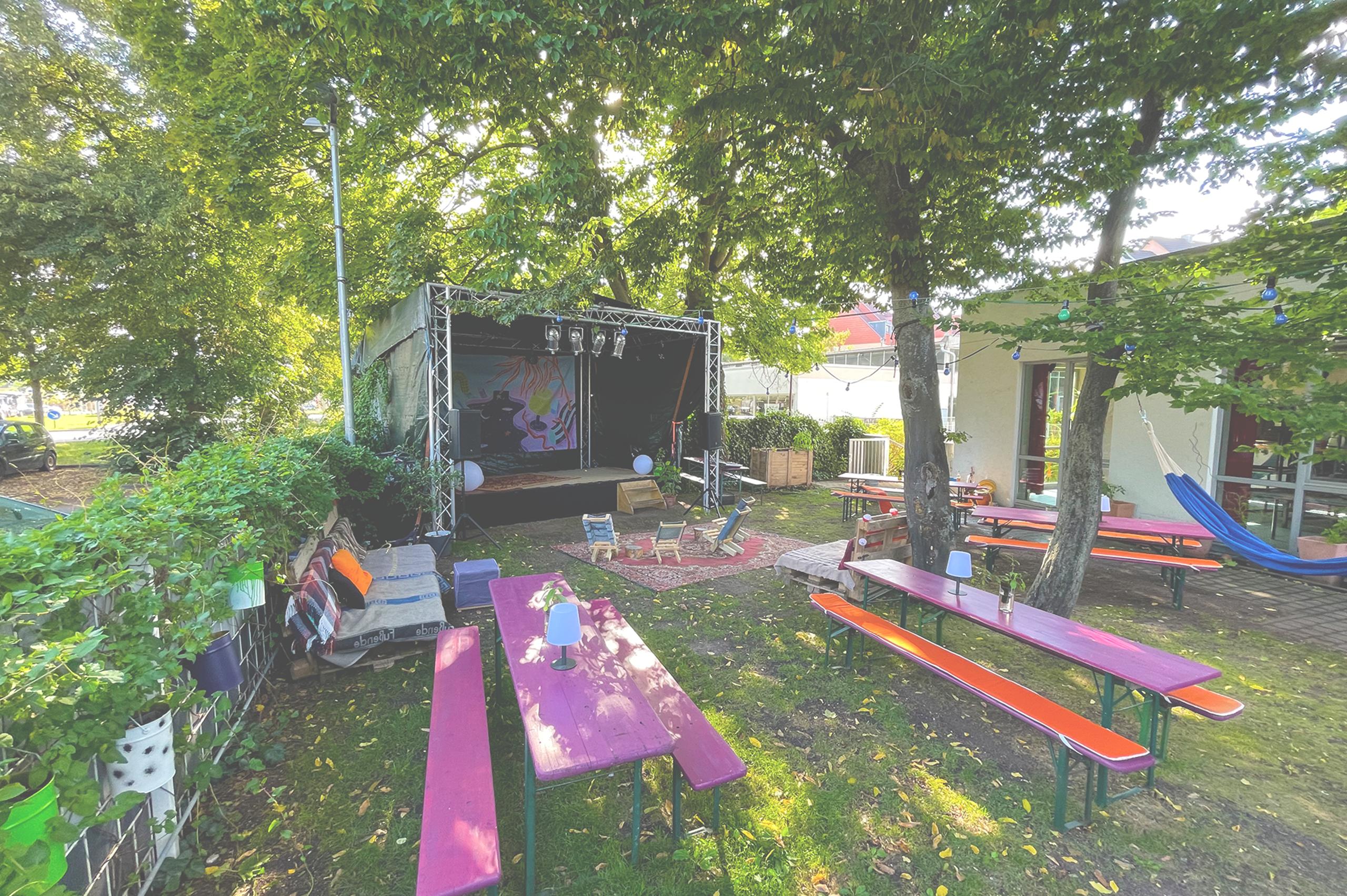 Foto vom Biergarten mit Außenbühne, Sitzgelegenheiten aus Palleten und Biertischgarnituren. An der Seite hängt eine Hängematte.
