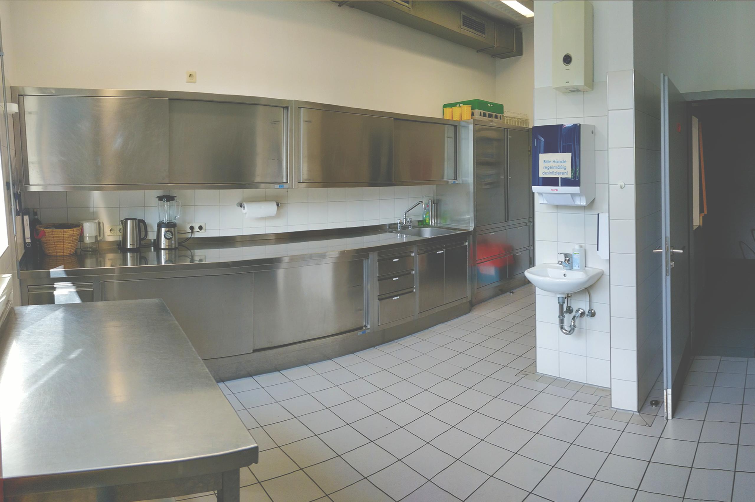 Foto der Inustrieküche mit Küchenschränken aus Metall, einer Spüle, einem Waschbecken. Mit Wasserkocher,und Mixer.